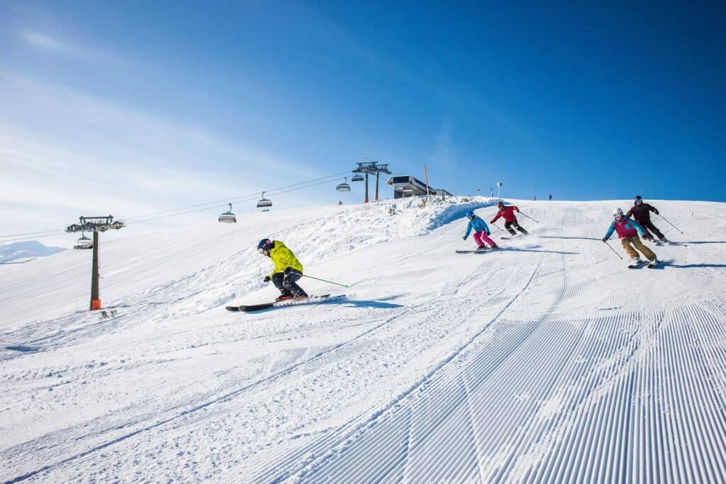 Gruppe Skifahrer auf einer Abfahrt im Skigebiet Flachau