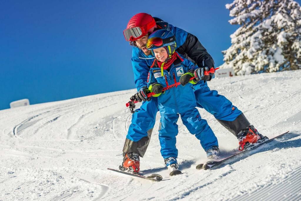 Skilehrer zeigt Jungen wie man Ski fährt